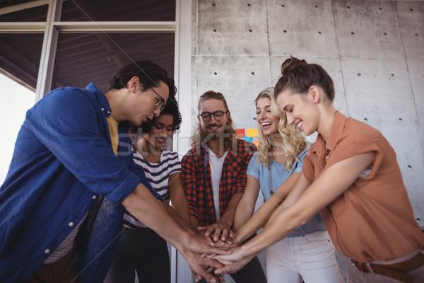 Happy business people stacking hands in office Stock photo © wavebreak_media