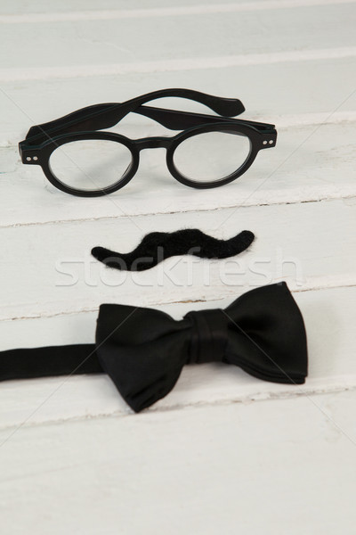 Bow tie, spectacles and fake moustache arranged on wooden plank Stock photo © wavebreak_media