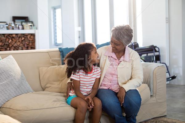 Smiling grandmother interacting with granddaughter in living room Stock photo © wavebreak_media
