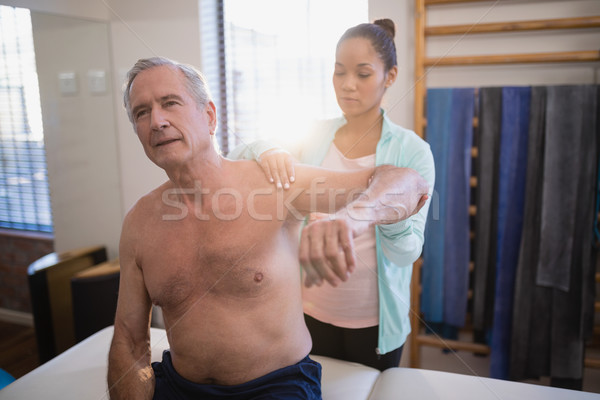 Shirtless senior male patient with arms raised receiving neck massage from female therapist Stock photo © wavebreak_media
