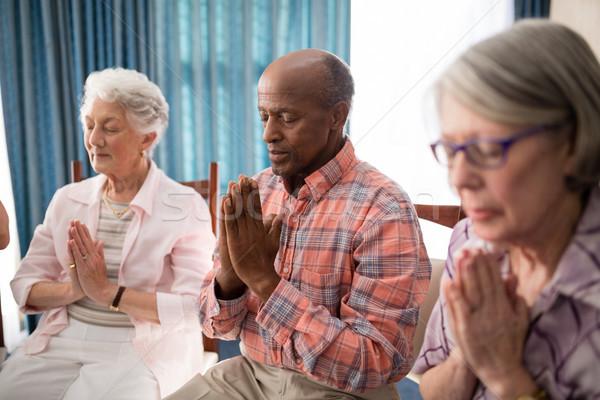 Senior man amidst women praying while sitting on chairs Stock photo © wavebreak_media