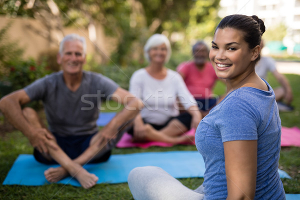 Smiling trainer sitting with senior people while exercising Stock photo © wavebreak_media