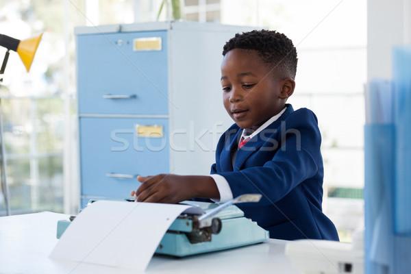 Boy imitating as businessman using typewriter Stock photo © wavebreak_media