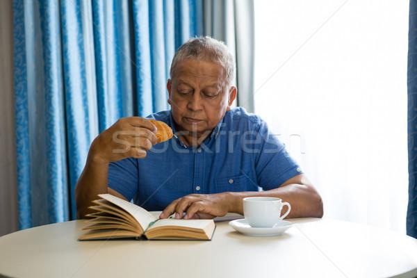Idős férfi eszik croissant olvas könyv Stock fotó © wavebreak_media