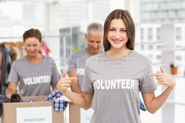 Sonriendo femenino voluntario senalando camisa retrato Foto stock © wavebreak_media
