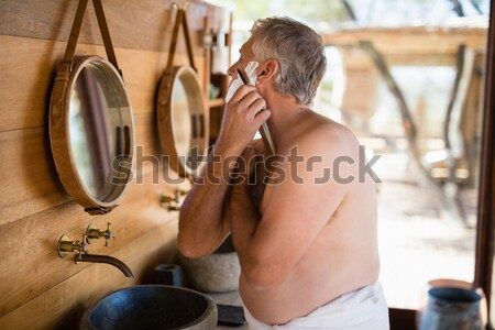Couple standing with arm around while shaving in cottage Stock photo © wavebreak_media
