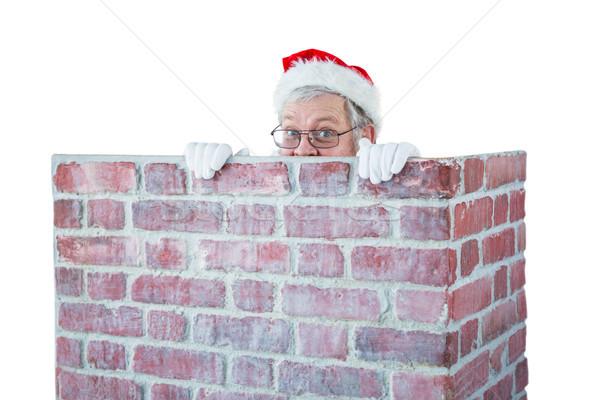 Santa claus hiding behind a chimney Stock photo © wavebreak_media