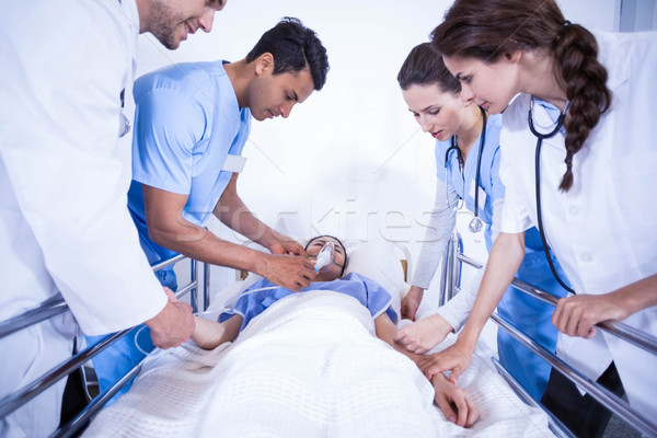 Orvosok megvizsgál beteg ágy kórház nő Stock fotó © wavebreak_media