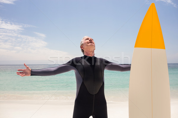 Happy senior man in wetsuit standing with arms outstretched  Stock photo © wavebreak_media