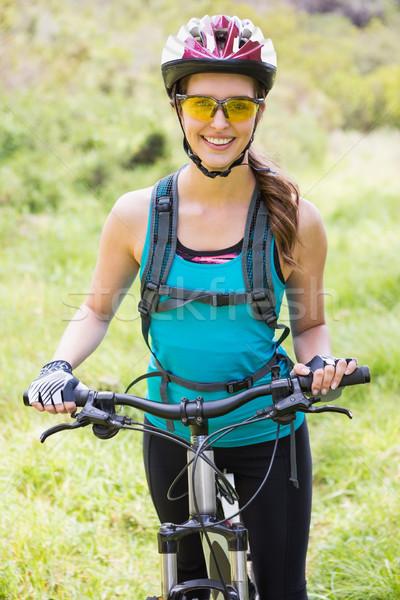 Smiling woman standing next to her bike Stock photo © wavebreak_media