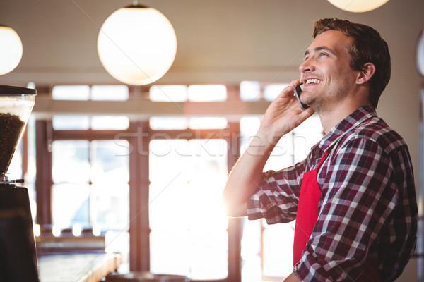 Garçom falante telefone móvel em pé contrariar homem Foto stock © wavebreak_media