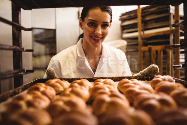 Portrait of female baker holding a tray of michetta Stock photo © wavebreak_media