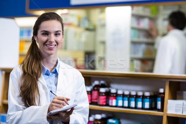 Pharmacist writing on notepad in pharmacy Stock photo © wavebreak_media