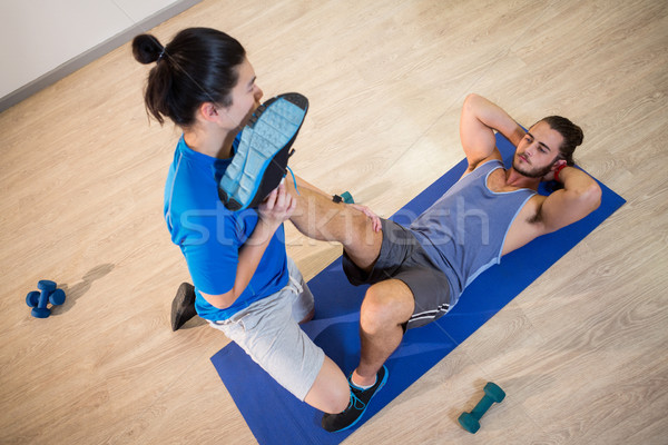 Yoga instructor helping fitness man with leg flexes Stock photo © wavebreak_media