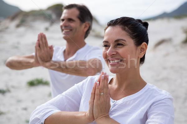 Couple performing yoga on beach Stock photo © wavebreak_media