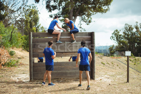 Female trainer assisting fit woman to climb over wooden wall during obstacle course Stock photo © wavebreak_media