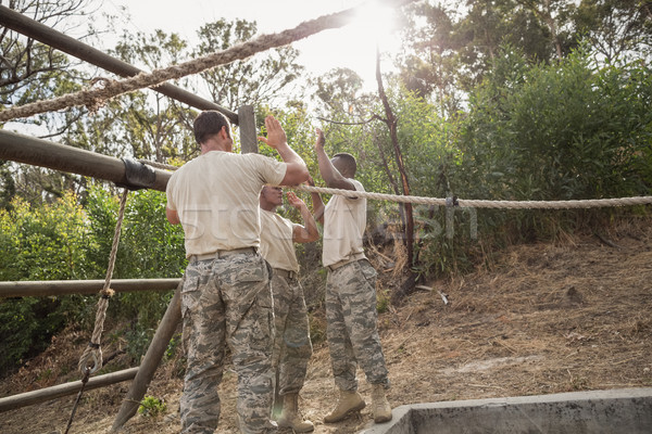 Young military soldiers giving after rope climbing during obstacle course Stock photo © wavebreak_media