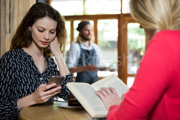 Jonge vrouwen telefoon lezing boek coffeeshop vrouw Stockfoto © wavebreak_media