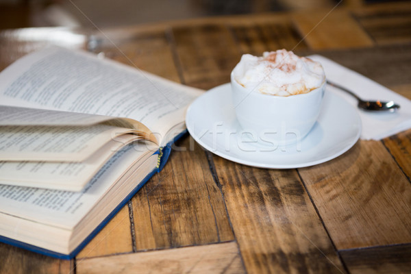 Coffee cup by open book on table in cafeteria Stock photo © wavebreak_media