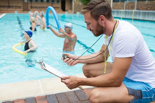 Swim coach looking at clipboard near poolside Stock photo © wavebreak_media