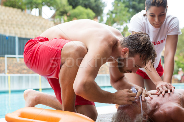 Lifeguards pressing chest of unconscious senior man Stock photo © wavebreak_media