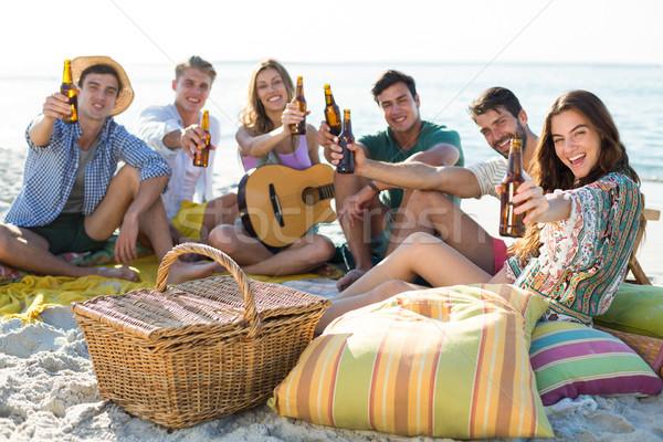 Friends having drinks while sitting at beach Stock photo © wavebreak_media