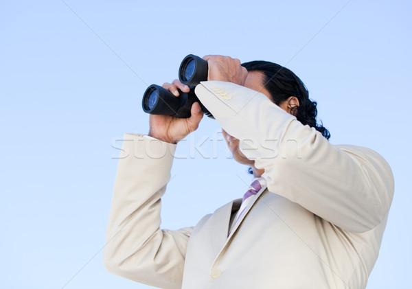 Portrait of an handsome business man looking through binoculars Stock photo © wavebreak_media