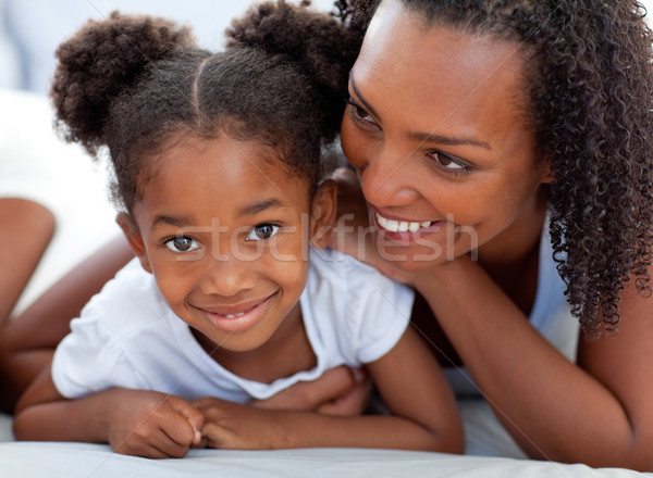 Attentive woman and her daughter relaxing lying down on bed Stock photo © wavebreak_media