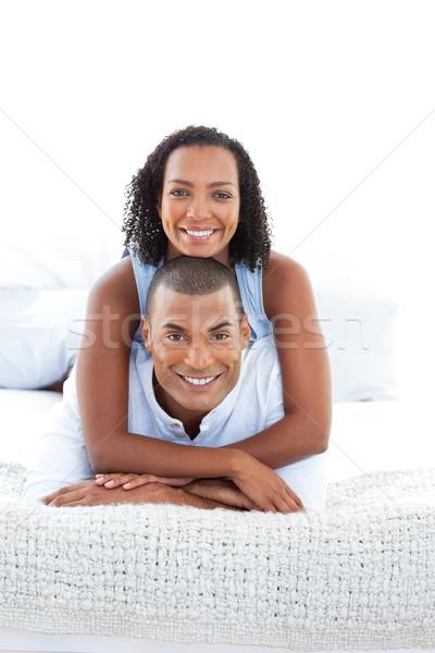 Portrait of a romantic couple cuddling lying down on bed Stock photo © wavebreak_media