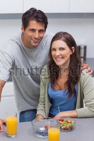 Romaantic couple eating fruit lying on their bed  Stock photo © wavebreak_media