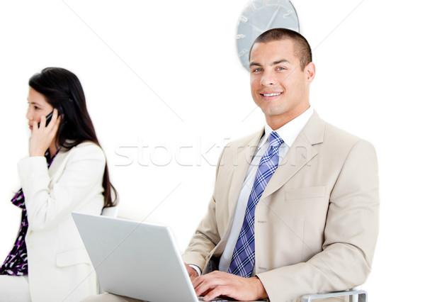 Bello imprenditore utilizzando il computer portatile sala di attesa imprenditrice telefono Foto d'archivio © wavebreak_media