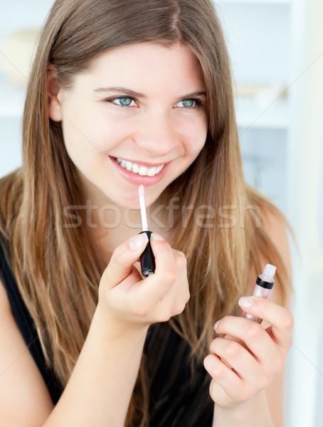 Smiling girl using lipstick at home Stock photo © wavebreak_media
