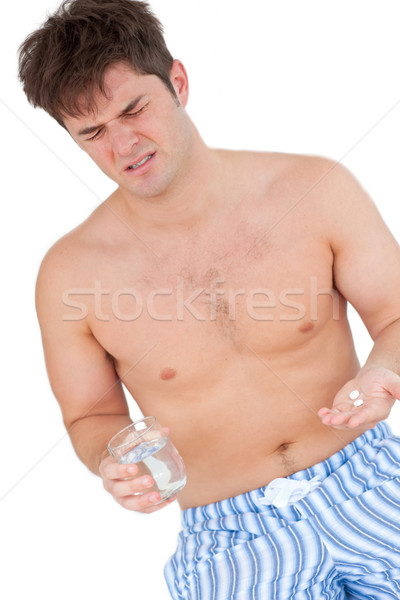 Młody człowiek posiedzenia bed szkła wody Zdjęcia stock © wavebreak_media