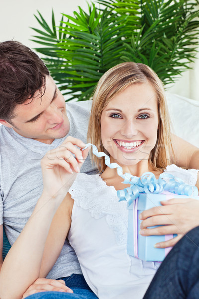 Happy woman unwrapping a present lying on the sofa with her boyfriend at home Stock photo © wavebreak_media