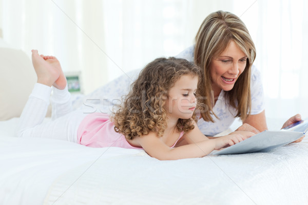 Young girl reading a book with her grandmother Stock photo © wavebreak_media