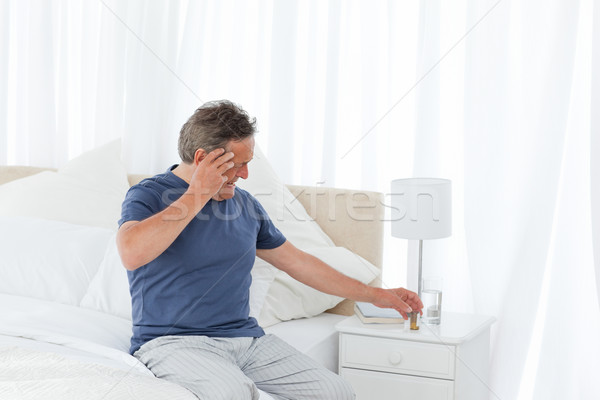 Man having a headache on his bed Stock photo © wavebreak_media