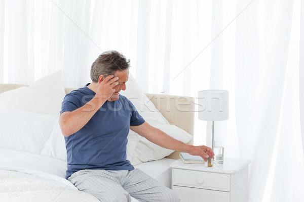 Stock photo: Man having a headache on his bed