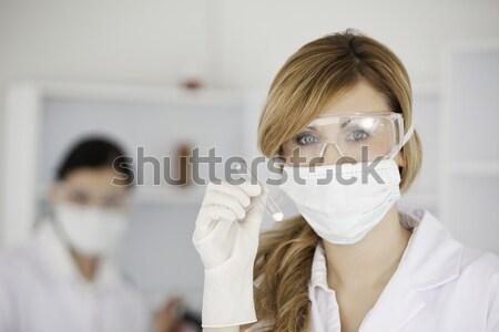 Blond-haired scientist wearing a mask and safety glasses and holding a  test tube in a lab Stock photo © wavebreak_media