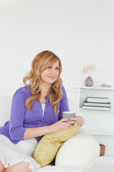 Pensativo mujer sesión sofá salón sonrisa Foto stock © wavebreak_media