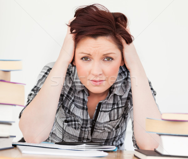 Good looking red-haired girl being upset while studying for an examination at her desk Stock photo © wavebreak_media