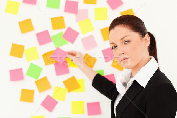 Komoly nő jegyzetek fehér fal iroda Stock fotó © wavebreak_media