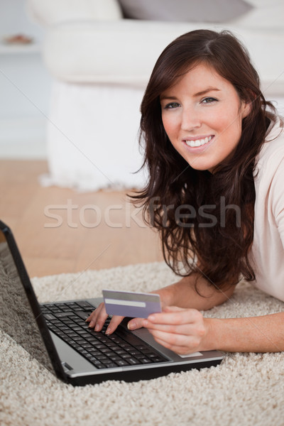 Young good looking woman making a payment with a credit card on the internet while lying on a carpet Stock photo © wavebreak_media