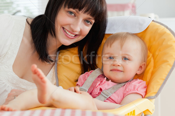 Good looking brunette woman posing with her baby while sitting in the kitchen Stock photo © wavebreak_media