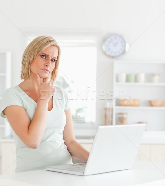 Wondering blonde woman looking at notebook in the kitchen Stock photo © wavebreak_media