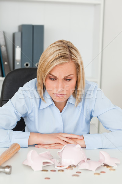 Sulking woman sitting in front of an shattered piggy bank in her office Stock photo © wavebreak_media