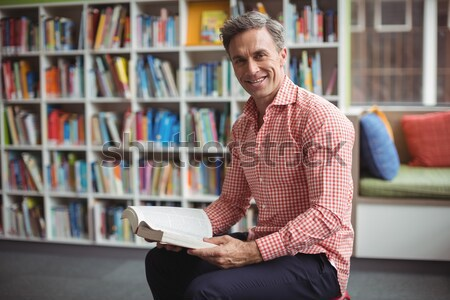 Portrait of a smiling male student holding a book in a library Stock photo © wavebreak_media