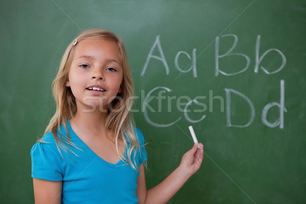 Stock photo: Smiling schoolgirl showing letters on a blackboard