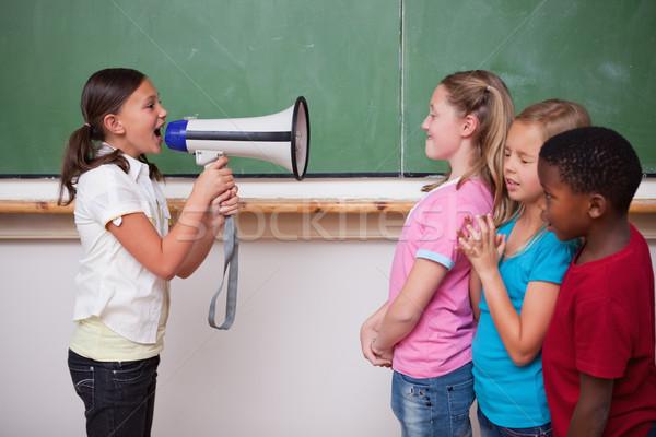 Iskolás lány kiabál megafon osztálytársak osztályterem kéz Stock fotó © wavebreak_media