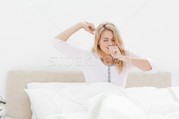 A woman in bed, leaning upright one arm stretching out and one hand covering her mouth as she yawns. Stock photo © wavebreak_media