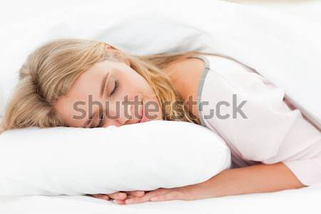 A woman resting in bed with her head on the pillow and her hands underneath it and her eyes are clos Stock photo © wavebreak_media